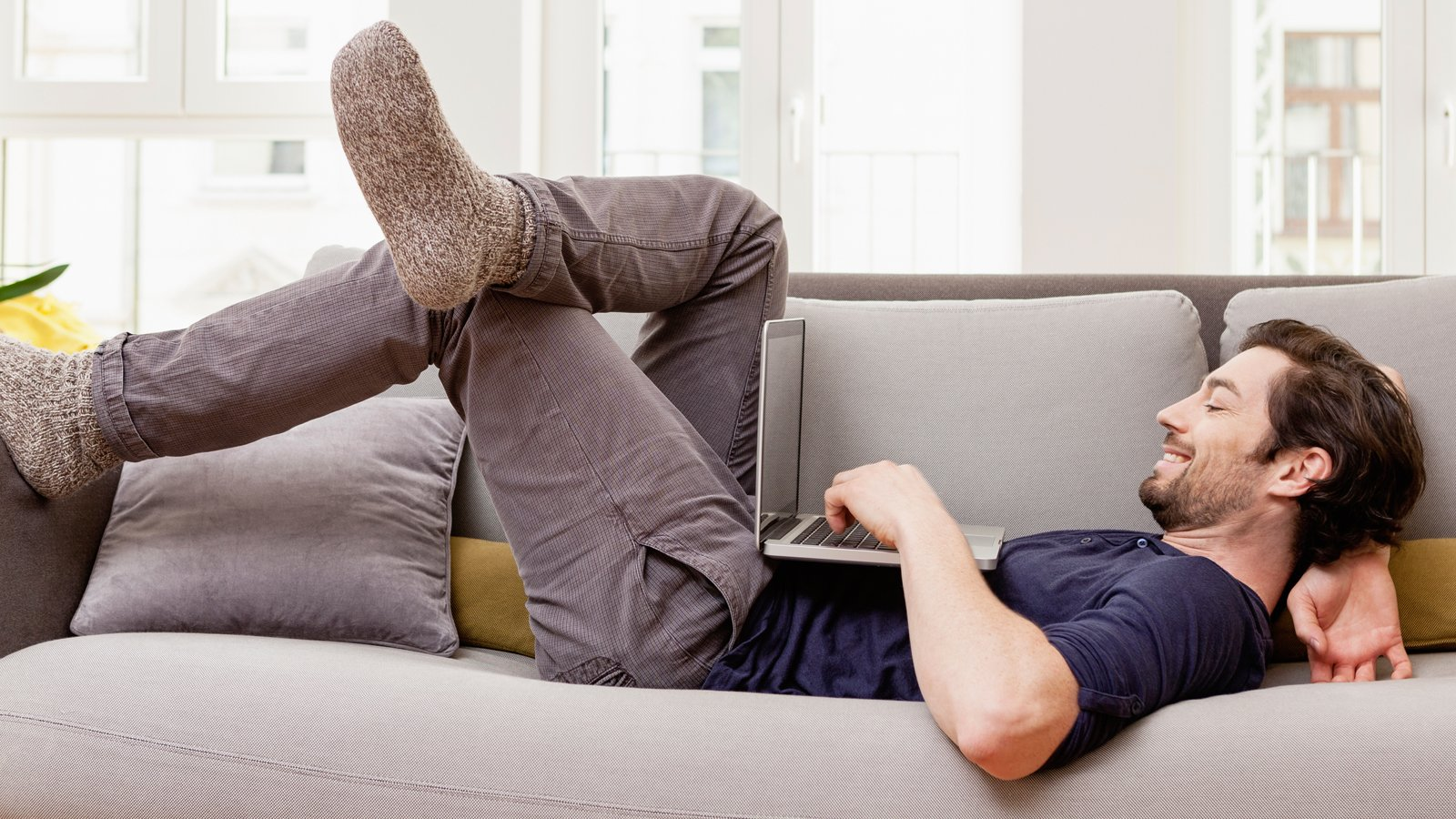 man lying down with laptop