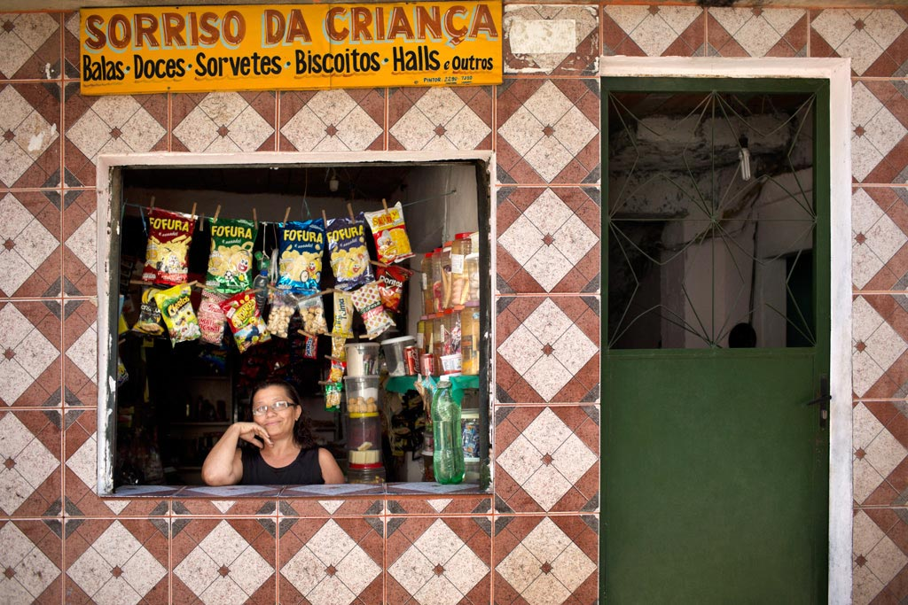 Woman at window counter of neighborhood store in Brazil.