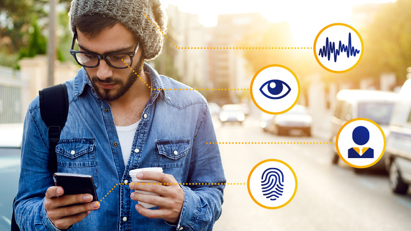 Man on city street using a smart phone with biometric symbols for voice analysis, iris recognition, behavior patterns, and fingerprint recognition.