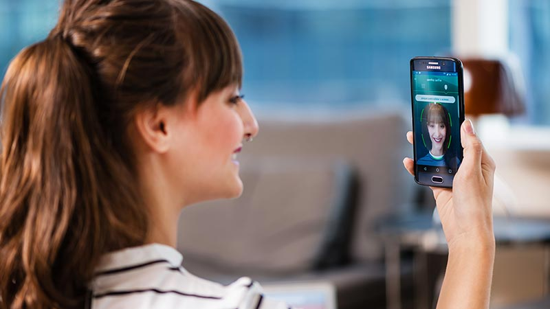 Woman using smart phone to calibrate facial recognition.